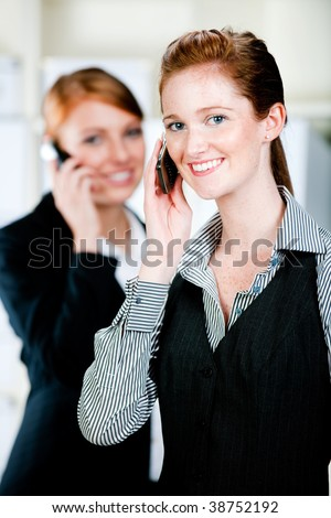 Two attractive caucasian businesswomen using their phones in the office