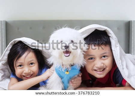 Two attractive children having fun with their dog at home while lying under blanket - stock photo