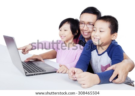 Two attractive children using a laptop computer on the table with their dad, isolated on white background - stock photo
