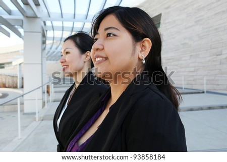 Two attractive Chinese business women at office building - stock photo