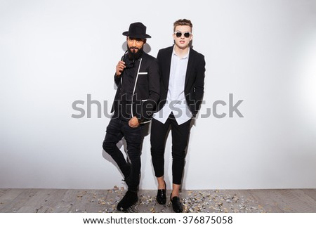 Two attractive confident young men in modern black suits standing over white background - stock photo