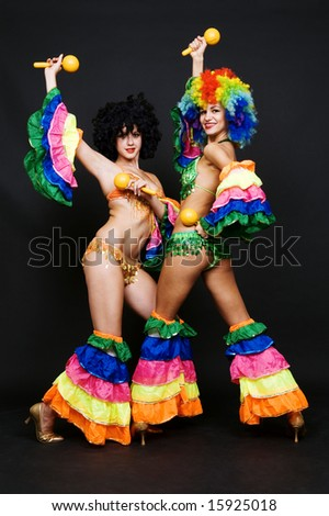 two attractive dancers with maraca over dark background - stock photo