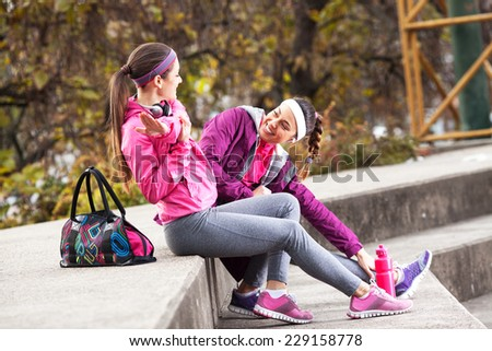 Two attractive female sitting and preparing for jogging. - stock photo