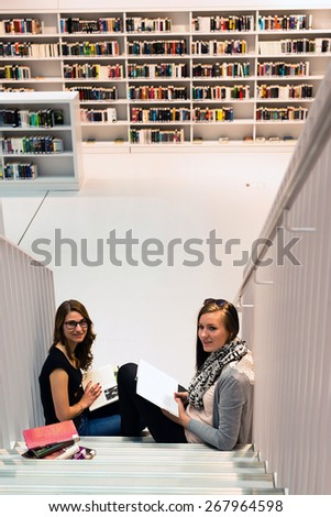 Two attractive female students are stuyding at the public library sitting on the stairs with books - stock photo
