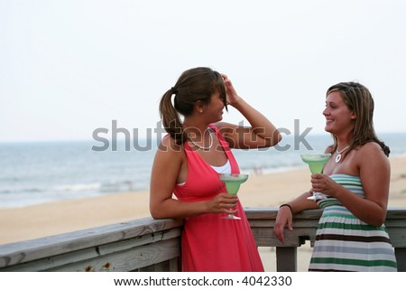 two attractive females have drinks overlooking the beach