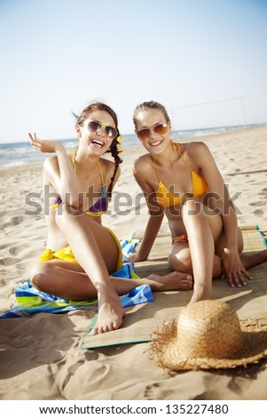two attractive females on the beach - stock photo