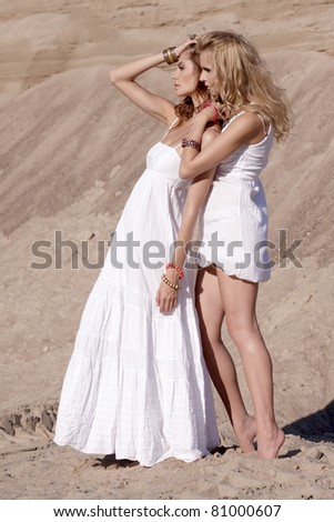 two attractive girl friends in white dresses standing in the desert - stock photo