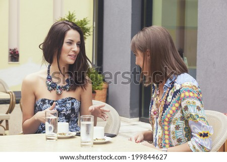 Two attractive girlfriends drinking coffee and talking in the cafe bar
