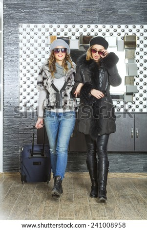 Two attractive girlfriends in hotel lobby - stock photo
