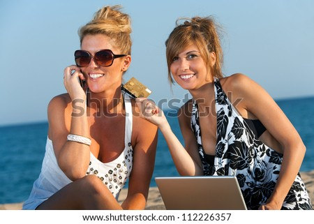 Two attractive girlfriends shopping on line with credit card at beach.
