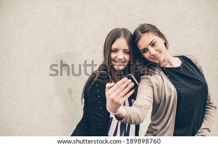 Two Attractive Girlfriends Taking Self Portrait with Their Phone Camera - stock photo