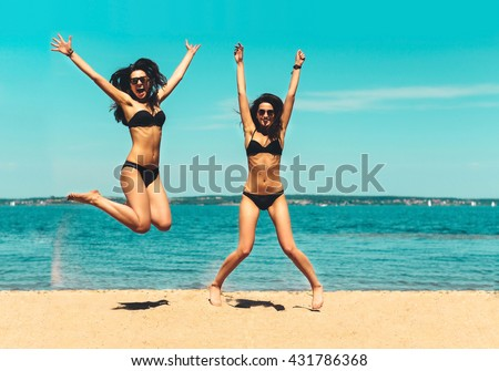 Two Attractive Girls in Bikinis Jumping on the Beach. Best Friends Having Fun, Summer vacation holiday Lifestyle. Happy women jumping freedom on white sand.   - stock photo