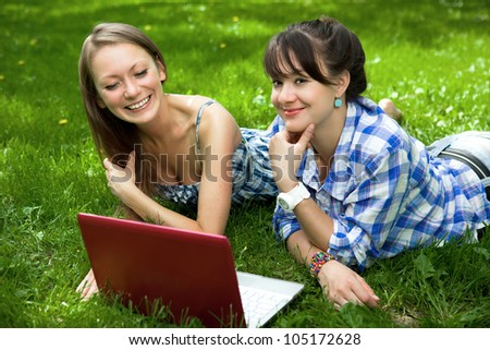 Two attractive girls on the grass with a laptop in the park