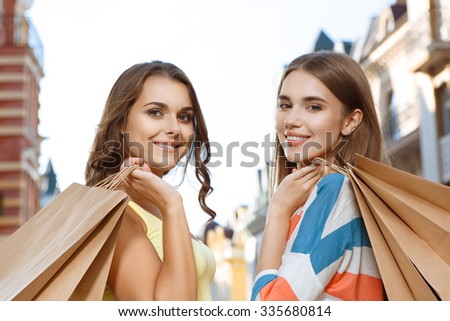 Two attractive girls walking in city with shopping bags - stock photo
