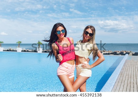 Two attractive girls with long hair are posing near pool on the sun. Brunette girl wears short pink shorts and T-shirt, blond wears yellow shorts and T-shirt. They are smiling to the camera. - stock photo