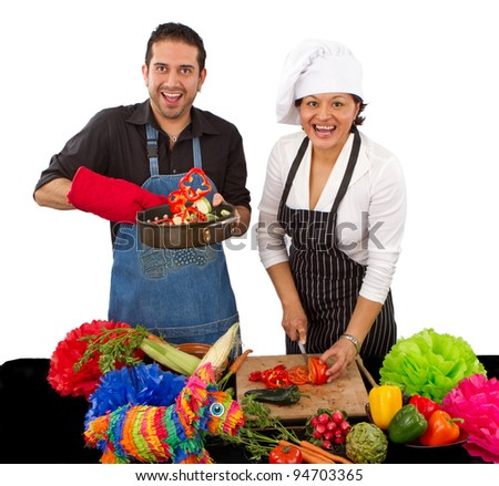 Two attractive happy chefs preparing for a Mexican celebration by cutting vegetables and flipping them in a frying pan. - stock photo