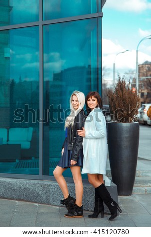 two attractive happy ladies brunette and blonde looking at the camera and smiling outdoors - stock photo