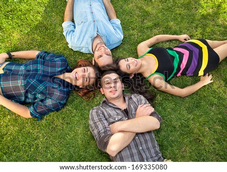 Two attractive happy teenage couples relaxing on the grass lying with their heads together looking up at the camera