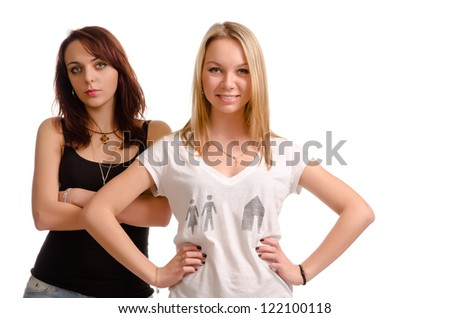 Two attractive jaunty young female friends posing standing together, half body studio portrait isolated on white - stock photo