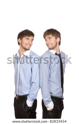 Two attractive positive smile young business people brother twins standing looking to each other, dressed in shirt, tie. Concept Success, isolated over white background - stock photo
