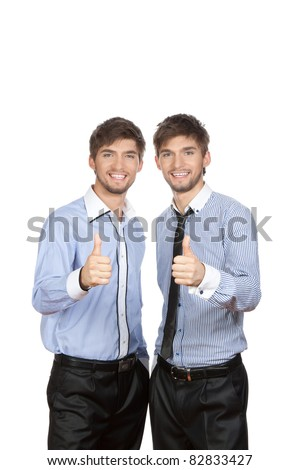 Two attractive positive smile young business people standing and holding hands with thumbs up gesture, dressed in shirt, tie. Concept Success, Approval, Good Work, isolated over white background