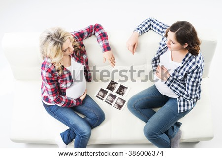 Two attractive pregnant women watching ultrasound photos. - stock photo