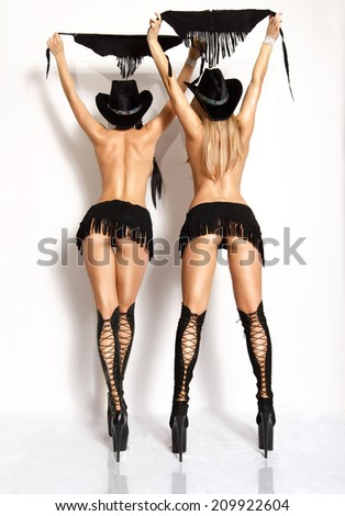 Two attractive sexy girls in fetish outfits.Studio shot - stock photo