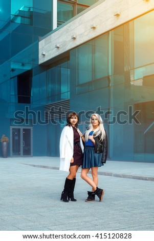 two attractive sexy ladies brunette and blonde looking at the camera outdoors. vertical photo  - stock photo