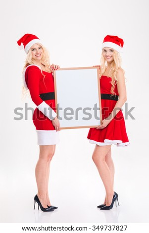 Two attractive sisters twins in santa claus costumes and hats standing and holding blank board over white background