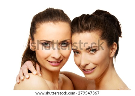Two attractive sisters with make up embracing.