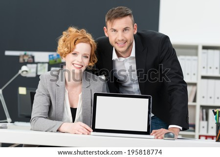 Two attractive smiling businesspeople displaying their team project on a blank tablet computer standing upright on a desk visible to the viewer - stock photo