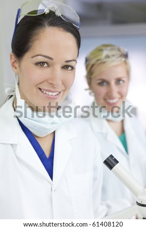 Two attractive smiling female scientists or women doctors wearing a white coats in a laboratory or hospital - stock photo