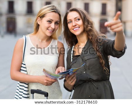 Two attractive smiling girls with luggage and map at city street