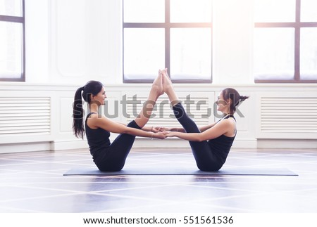 Two Attractive Sport Girls Work Out Nauka Asana Boat Yoga Pose On Black Mat In Fitness