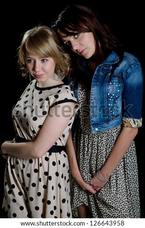 Two attractive trendy young woman in stylish dresses posing close together on a dark studio background - stock photo