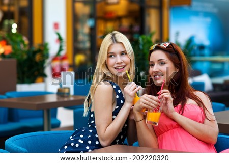 two attractive woman friends drinking juice in the bar - stock photo
