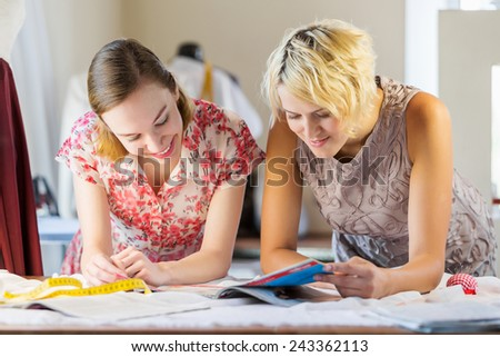 Two attractive women at dressmakers choosing design
