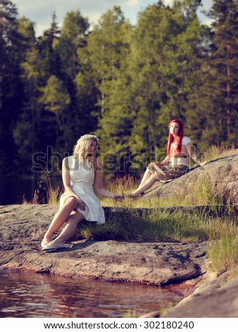 Two attractive women sits on the rock and dreaming, summer day on the lake - cross processed image - stock photo