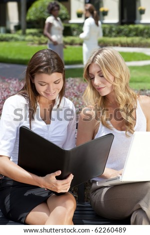 Two attractive you businesswomen or female executives meeting outside with laptop computer and folder - stock photo