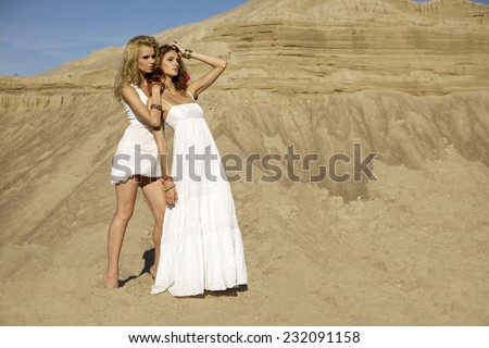 Two attractive young adult girls friends - blond and brunette sensuality woman over sand background - stock photo