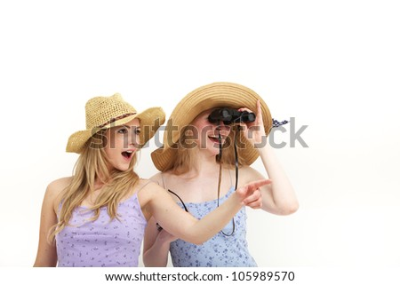 Two attractive young female tourists in sunhats Two attractive young female tourists in sunhats with binocluars looking into the distance while exclaming and pointing in excitement