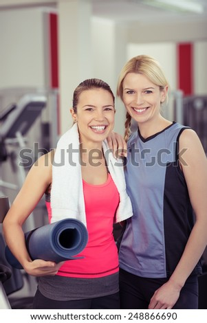 Two attractive young fit female friends at the gym standing side by side with a rolled up exercise mat smiling happily at th camera