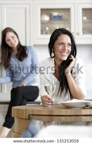 Two attractive young friends laughing and drinking wine in their kitchen.