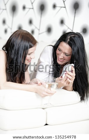 Two attractive young friends on a sofa reading texts. - stock photo