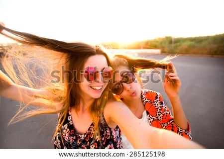 Two attractive young girl friends standing together and posing on camera.Brunette having fun and showing sign with her hand.photography at sunset.two women taking selfie with mobile phone with fisheye - stock photo