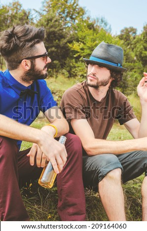Two Attractive young People hanging out in nature and drinking beer - stock photo