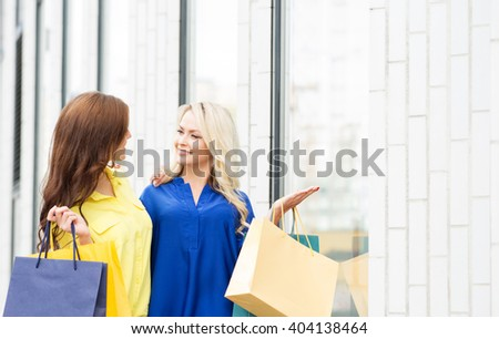Two attractive young shopaholics with shopping bags outside. Blond pointing at clothes in store window. - stock photo