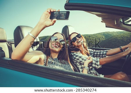 Two attractive young women dtaking selfe in a convertible car - stock photo