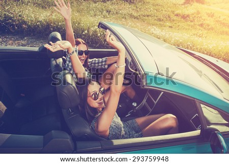 Two attractive young women in a convertible car - stock photo