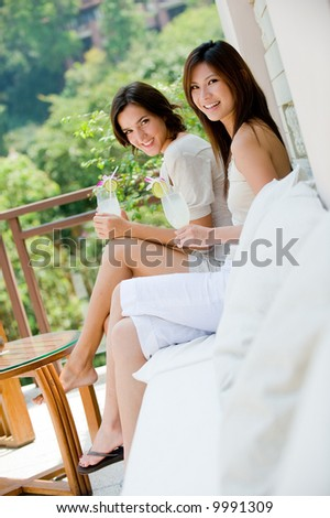 Two attractive young women sitting on a sofa outside with tropical drinks - stock photo